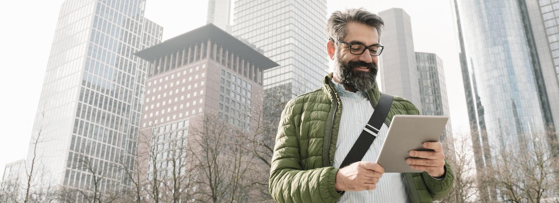 Mann schaut auf Tablet vor der Skyline von Frankfurt