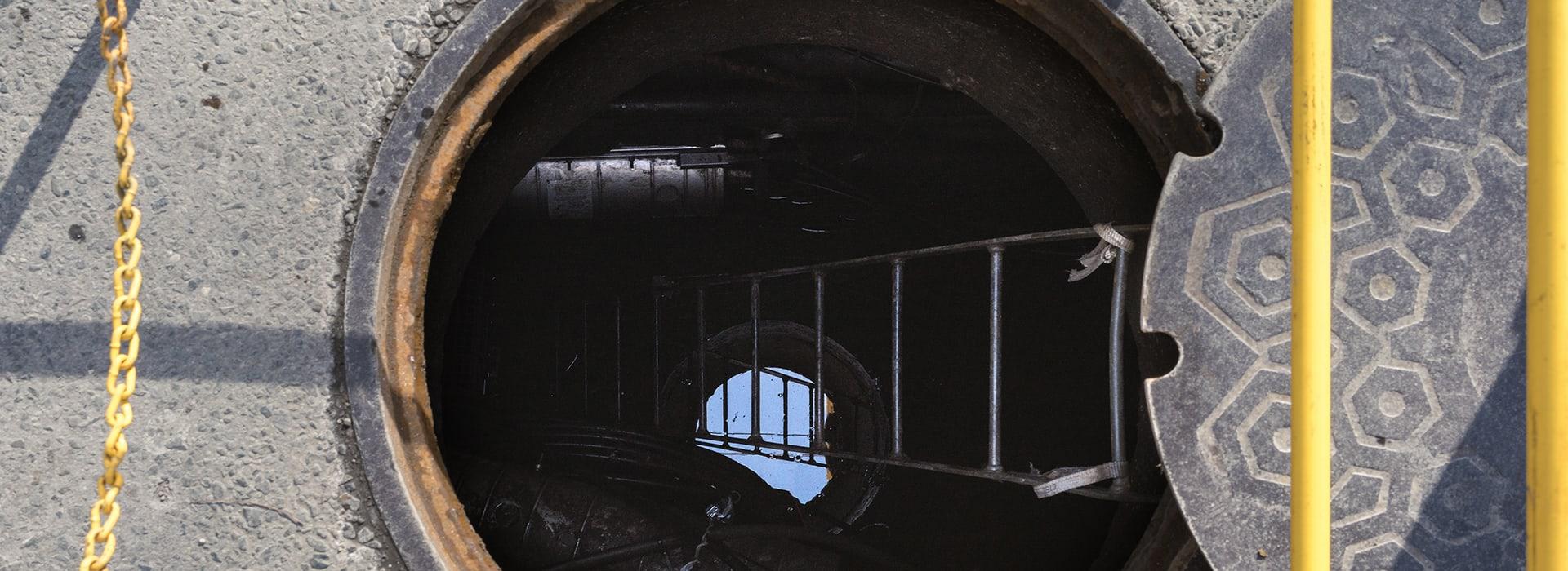 Geöffneter Schacht mit Leiter