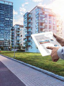 Tablet vor Mehrfamilienhäusern